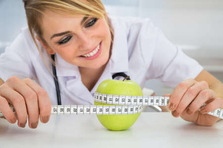 job loss: Happy Female Dietician Measuring Green Apple With Measuring Tape