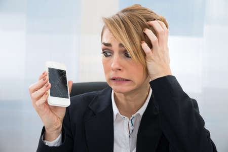 broken telephone: Close-up Of Worried Businesswoman Holding Broken Screen Smartphone In Office Stock Photo