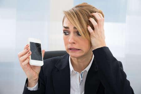 zellen: Close-up Von Besorgte Gesch�ftsfrau, Broken Screen smartphone im B�ro