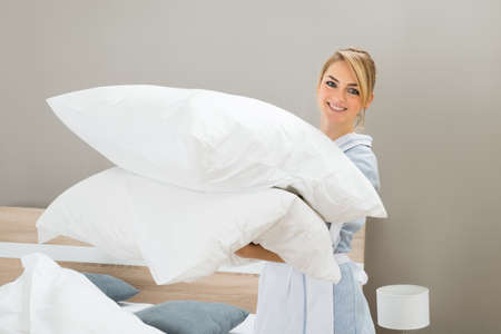 hotel service: Happy Female Housekeeping Worker With Pillows In Hotel Room