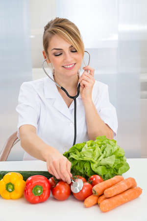 dietitian: Happy Female Dietician Examining Fresh Vegetables With Stethoscope