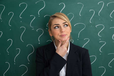 business attire teacher: Thoughtful Businesswoman In Front Of Chalkboard With Question Mark Sign