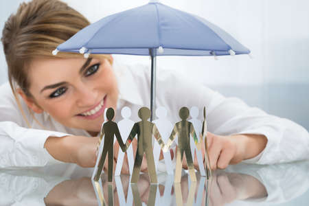 interlinked: Young Happy Businesswoman Protecting Cut-out Figures With Small Umbrella