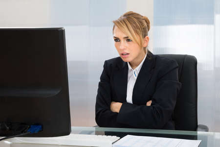 workplace wellness: Young Businesswoman With Arm Crossed Looking At Computer In Office Stock Photo