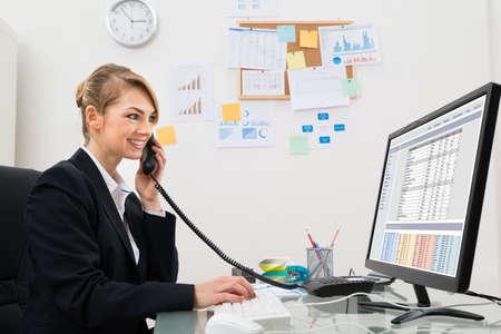hoja de calculo: Empresaria joven que habla en el teléfono delante del ordenador