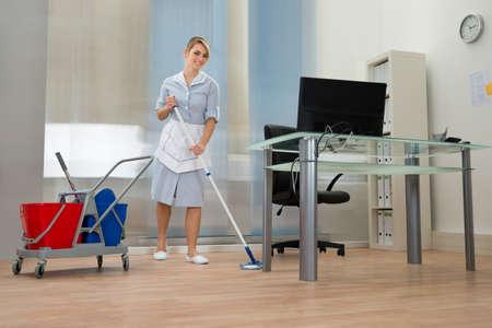 professionnel: Jeune Bonne Femme de ménage nettoyant pour sols Dans Office