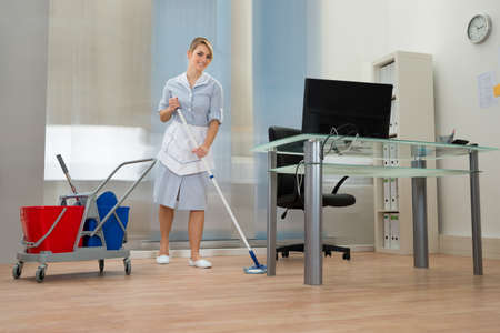 Office uniforms: Joven feliz Mujer criada Suelo Limpieza En Office
