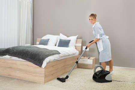 personal de limpieza: Mujer Ama de llaves Limpieza Alfombra Con Aspiradora En La Habitación