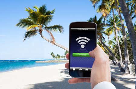 ビーチでの携帯電話の Wifi と人の手のクローズ アップ