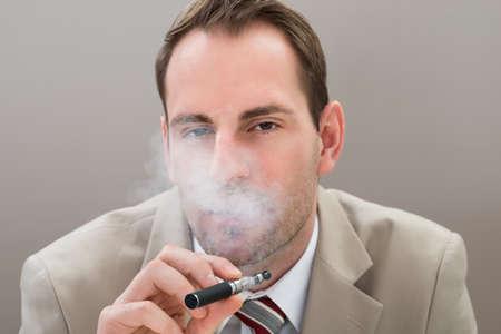 vaporized: Portrait Of Young Businessman Smoking Electronic Cigarette Stock Photo
