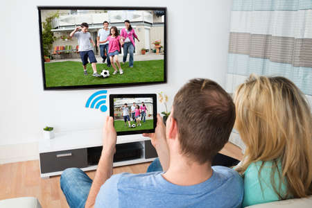 television: Couple Connecting Television And Digital Table Through Wifi Signal At Home Stock Photo