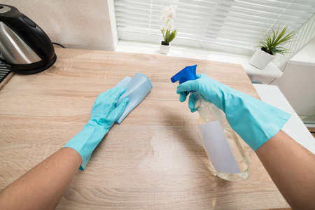Mani persona in blu guanto di pulizia da cucina in legno Piano di lavoro Archivio Fotografico - 39679462