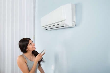 heat home: Young Happy Woman Holding Remote Control Air Conditioner In House