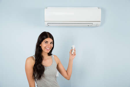 heat home: Happy Woman Holding Remote Control In Front Of Air Conditioner At Home
