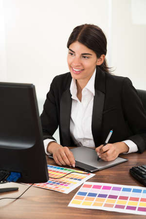 web designers: Female Designer Using Graphic Tablet With Color Sample At Desk