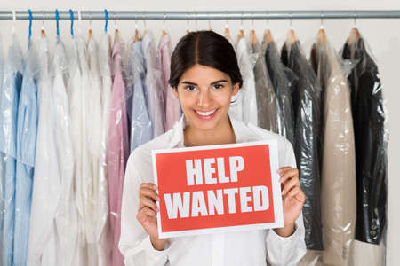 Young Happy Female Store Owner Holding Board With Text Help Wanted photo