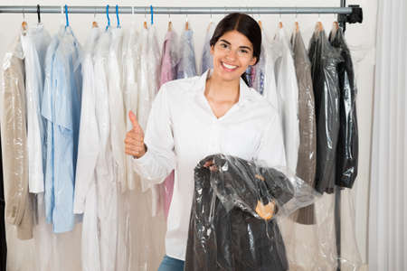 Young Happy Woman Holding Suit In Menswear Shop