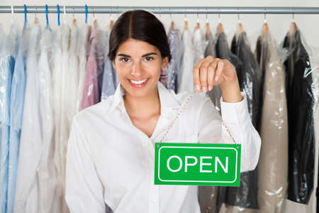 Young Happy Female Store Owner Holding Open Sign Board photo