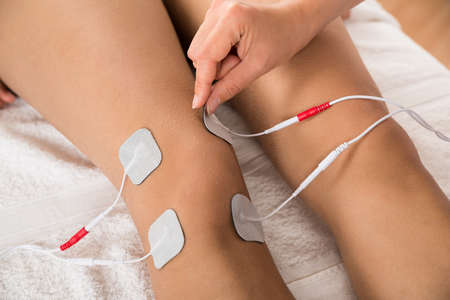 therapeutics: Close-up Of Therapist Placing Electrodes On Womans Knee