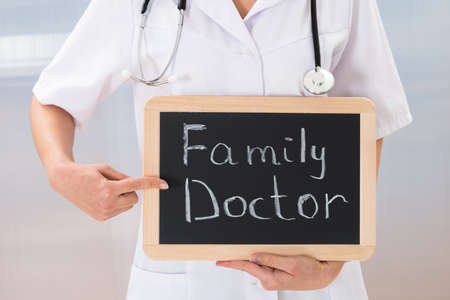 Close-up Of Female Doctor Showing Slate Chalkboard With Text Family Doctor photo
