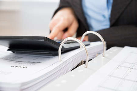 audit: Close-up Of Businessperson Calculating Tax In Office