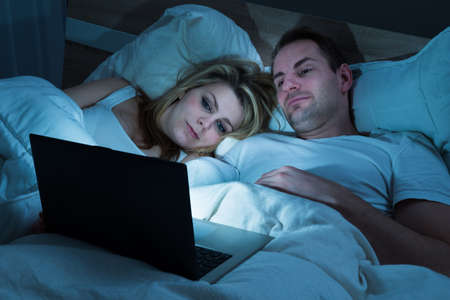 woman watching tv: Couple Lying In Bed With Blanket Looking At Laptop