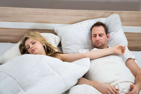 wife and husband: Couple Sleeping With White Duvet In Bed At Home