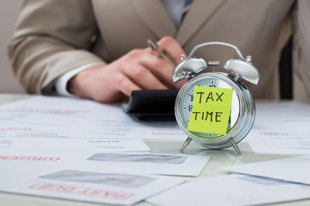 tax: Close-up Of Businessman With Tax Time Reminder Note On Alarm Clock At Desk