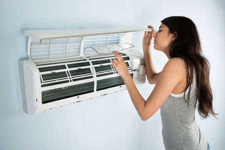 and the air: Young Woman Checking Air Conditioner In House