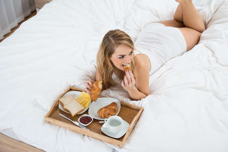 High Angle View Of A Woman Lying On Bed Having Breakfast