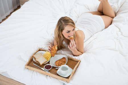 vysoký úhel pohledu: Vysoký úhel pohled na ženu ležící na posteli snídal