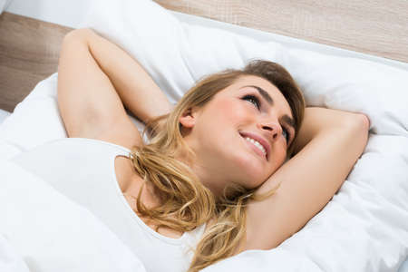 rested: High Angle View Of A Young Woman Lying On Bed Daydreaming Stock Photo