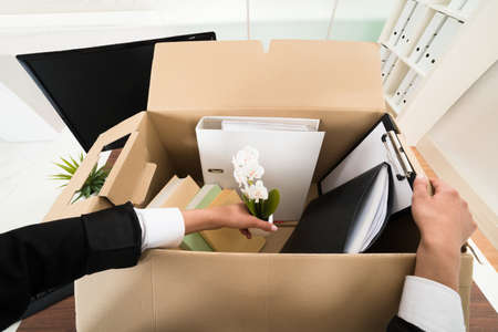 High Angle View Of Businesswoman Packing Personal Belonging In Box Stock Photo