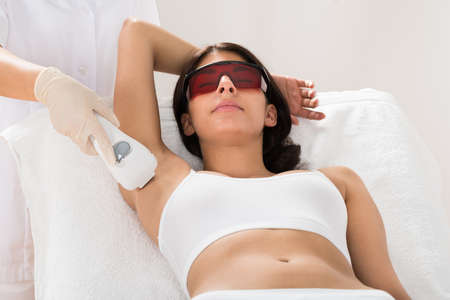 beauty treatment clinic: Woman Receiving Epilation Laser Treatment On Armpit At Beauty Clinic