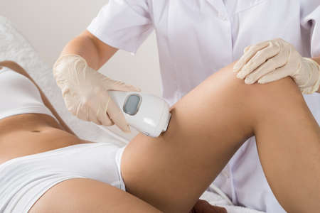depilation: Close-up Of Woman Having Laser Treatment At Beauty Clinic On Thigh