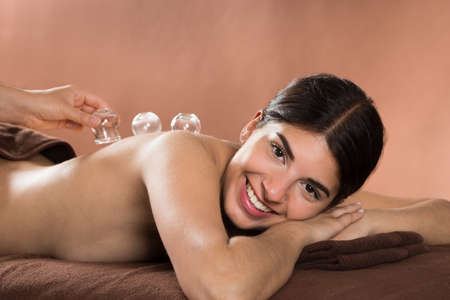 cupping therapy: Acupuncture Therapist Placing Cup On The Back Of A Female Patient