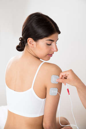 stimulator: Close-up Of Young Woman Getting Electrodes Therapy On Hand