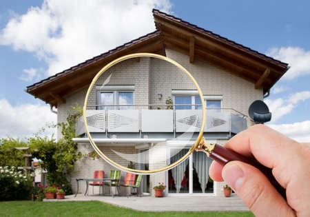 Person Hand With Magnifying Glass Over Luxury House Foto de archivo