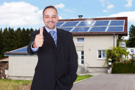 Happy Businessman With Thumbs Up Standing In Front Of House photo