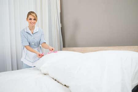 housekeeper: Feliz Mujer Ama de casa que adorna la cama con p�talos Foto de archivo