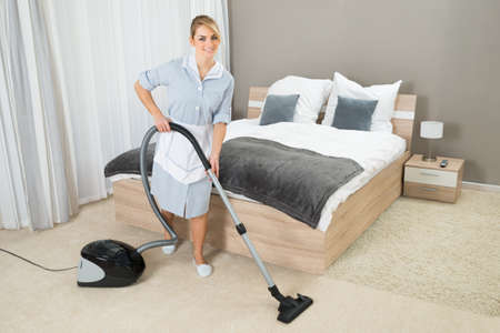Female Housekeeper Cleaning Rug With Vacuum Cleaner In Hotel Room Archivio Fotografico