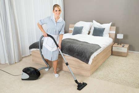 Female Housekeeper Cleaning Rug With Vacuum Cleaner In Hotel Room Foto de archivo