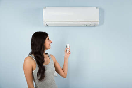 Young Happy Woman Using Remote Control Of Air Conditioner Reklamní fotografie