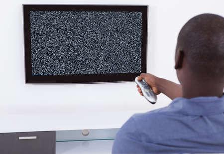 gente viendo television: Hombre con teledirigido delante de la televisión sin señal Foto de archivo