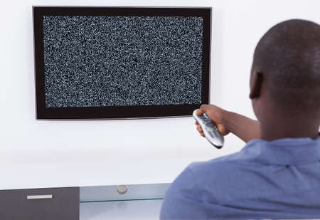 black button: Man With Remote Control In Front Of Television With No Signal