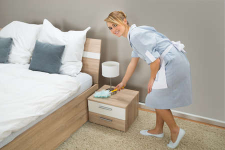 orden y limpieza: Mucama de Hotel En Uniforme Utiliza un plumero para quitar el polvo en el dormitorio