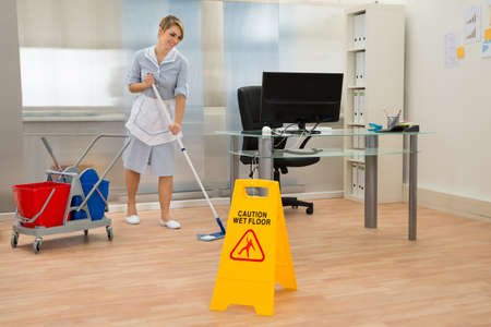Young Maid Cleaning Floor With Mop In Office Standard-Bild