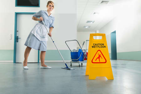 cleaning lady: Happy Female Janitor With Mop And Wet Floor Sign On Floor Stock Photo