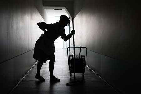 mopped: Silhouette Of Female Maid With Mop Suffering From Backache In Corridor