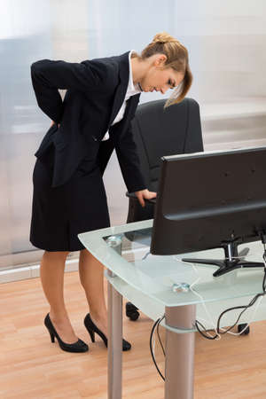backpain: Young Businesswoman Standing Near The Desk And Having Backpain Stock Photo